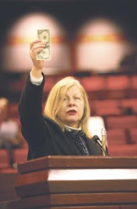 Doris Ray holds up $1 to contrast the percentage of funds spent in Virginia on home and community based services versus the $3 spent on institutional care for individuals with disabilities.